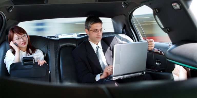 Assistant and Executive sitting in the back of a limousine
