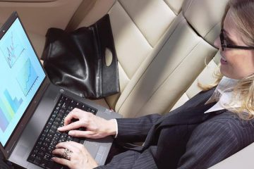 Businesswoman working on laptop in limousine