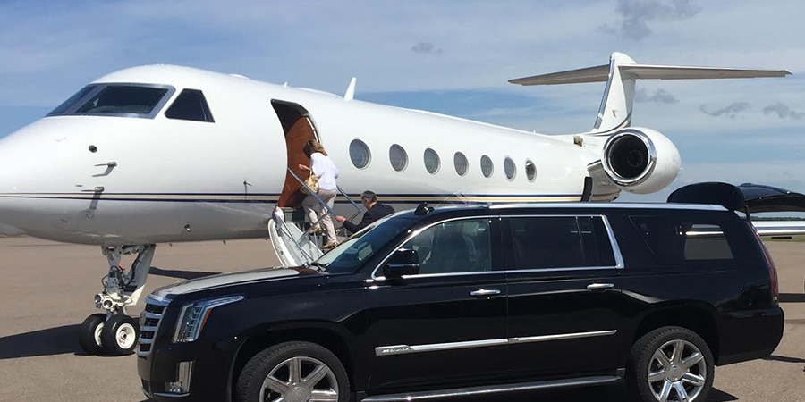 Executives getting out of black limousine and getting onto white jet