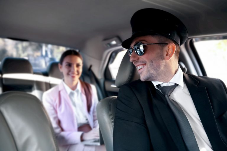 Chauffeur speaking to client in back seat of limousine