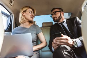 Low angle view of businessman and assistant working in car with laptop and smartphone