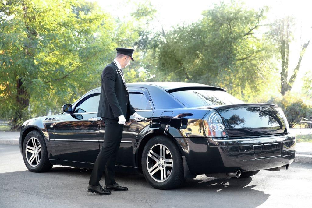 Chauffeur opening back door of black limousine