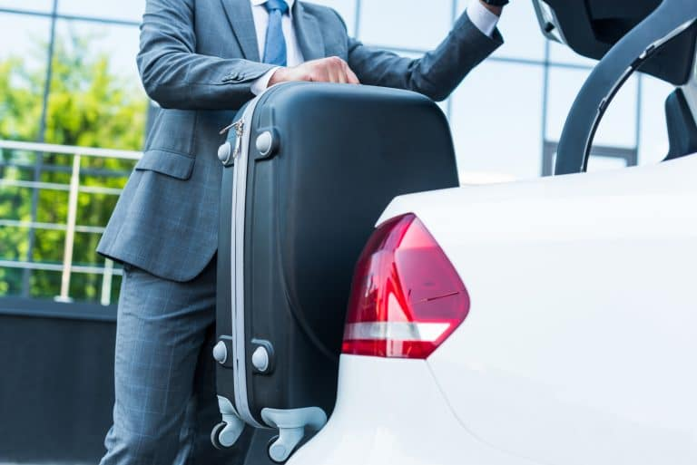 Chauffeur placing luggage in boot of limousine