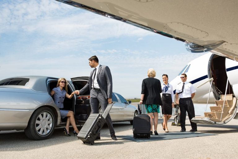 woman getting out a limo on the tarmac with a man helping her and flight crew standing outside the plane